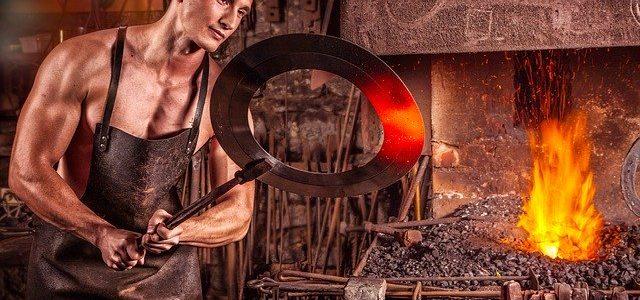 mann beim schmieden und metall schneiden